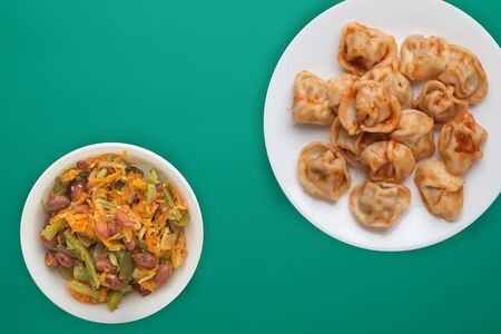 dumplings on a white plate against a green background. Dumplings meat in tomato sauce with vegetable salad top view. Asian cuisine