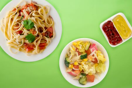 spaghetti on a white plate with vegetable salad  top view. spaghetti tomatoes, onions, cabbage on a light green  background. healthy food flat lay
