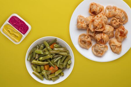 dumplings on a white plate against a yellow background. Dumplings meat in tomato sauce with vegetable salad top view. Asian cuisine