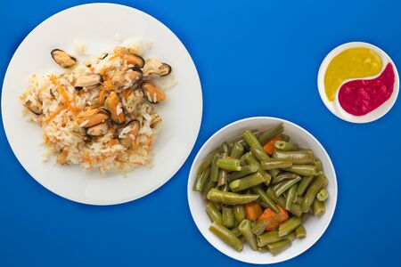 rice with mussels and carrots on awhite  plate. rice with mussels and carrots on a blue  background. rice with vegetable salad and sauce top view.asian food flat lay