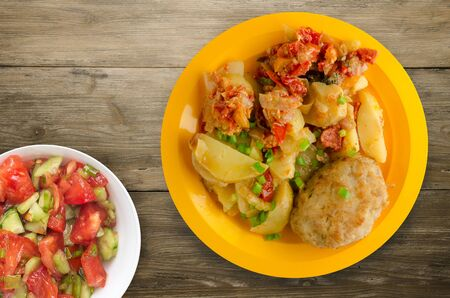 Cutlets with potatoes and stewed tomatoes. cutlet on a plate on a wooden   写真素材