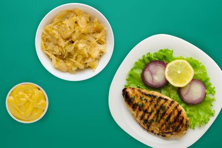 grilled chicken with vegetables lemon, salad, onion) on a green background. grilled chicken fillet on a plate in a vegetable salad top view.flat lay 写真素材