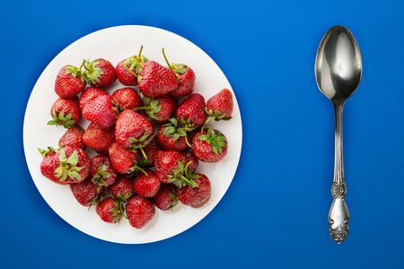 strawberries on a white plate top view. Strawberries on blue background. Healthy food. vegan food.