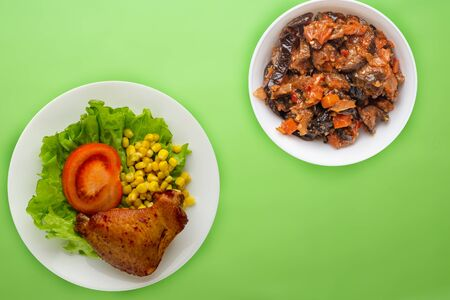 chicken wing with lettuce, corn and tomatoes on a white plate. chicken wing with vegetable salad   on a lime background top view 写真素材