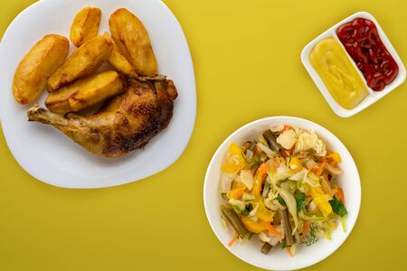 grilled chicken and french fries on a white plate on a yellow background with vegetable salad and sauce. Fast food top view. unhealthy food Foto de archivo - 135498505