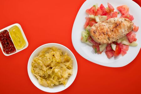 Grilled chicken breast with tomato salad, cucumbers and onions. Grilled chicken breast on a white plate on a  red green background. fried chicken breast top view.flat lay Foto de archivo - 135498673