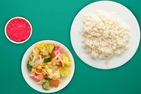 white rice on a white  plate. rice with vegetable salad  on a green  background top view .asian food Stock fotó