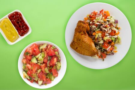 fried chicken thighs with vegetables on a white plate on the lime background. fast food with vegetable salad top view. unhealthy food.flat ley Foto de archivo - 135498681