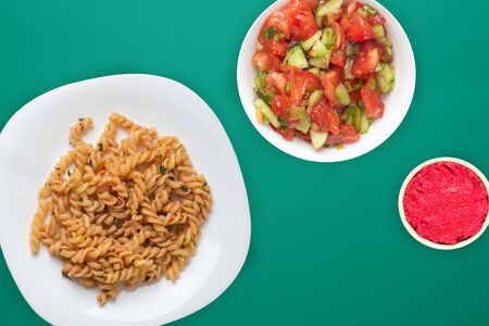 pasta on a white plate in tomato sauce with vegetable salad on a green background. Mediterranean cuisine top view. healthy food. flat lay