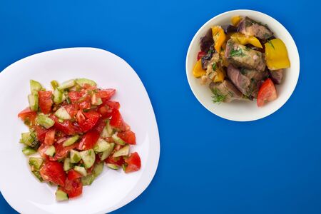 Vegetarian salad with cucumbers, tomatoes and green onions. Vegan salad on a white plate on a blue background.healthy vegetable breakfast top view.flat lay