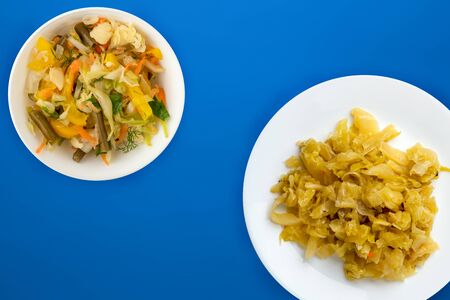 stewed cabbage in a white plate on a blue background. stewed cabbage top view. healthy eating. vegetarian food .flat lay