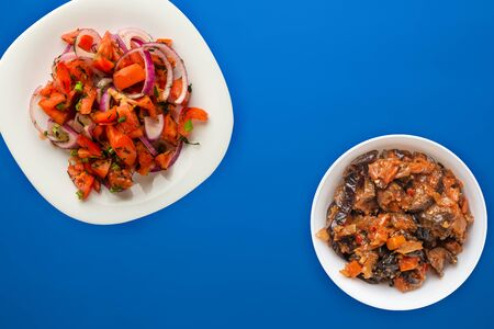 Vegetarian food. tomatoes, onions, dill on a white plate on a blue background. healthy food.flat lay