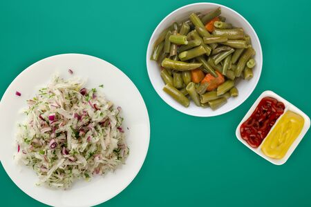 daikon salad, onion and dill on a green background. salad on a white plate. vegetarian food. healthy eating 写真素材