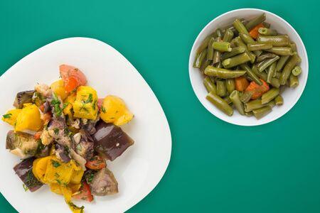 vegetarian food. Sauteed eggplant on a plate. healthy food on green backgroun.flat lay