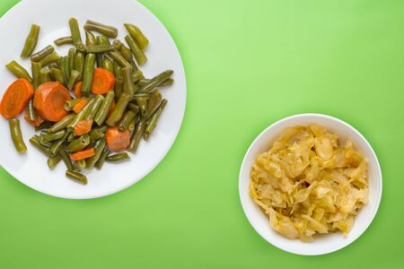 Green beans with garlic carrots on a white plate on a lime background. green beans with carrots with vegetable vegetarian salad and sauce top view. healthy vegetarian food.flat lay 写真素材