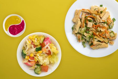 salad with soy asparagus and carrots, cucumbers and dumplings on a white plate. vegetarian soy salad on a plate on a yellow background. healthy eating top view.flat lay