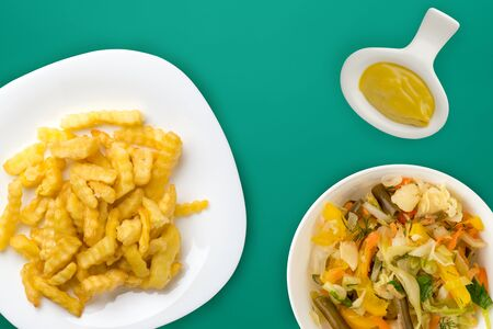french fries on a white plate in the green background. french fries with vegetable salad fast food top view. unhealthy food
