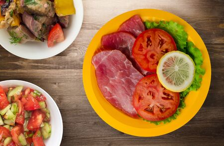ham with salad, tomato and lemon on a yellow  plate. ham on a wooden background .ham top view