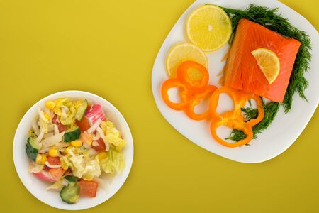 red fish with dill, pepper, lemon on a white plate on the yellow background. red fish with vegetable salad .sea food. flat lay