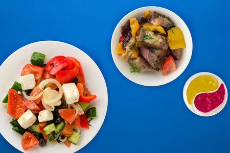 Greek salad on a blue background. Greek salad on a white plate top view. healthy food.flat lay