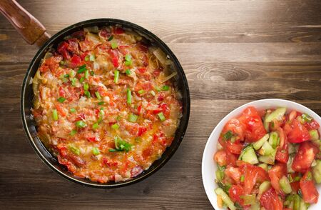 Stewed tomatoes with onions in a plate on a wooden background. stewed tomatoes with onion top view. vegetarian food