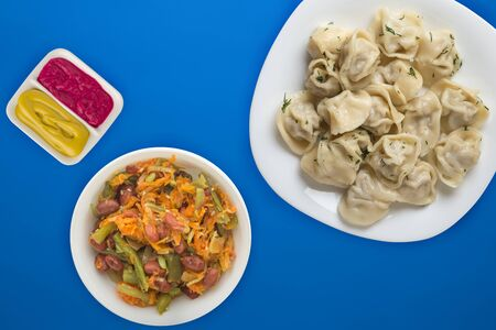 dumplings on a white plate on a  blue background. Top view of dumplings with vegetable salad. Asian cuisine flat lay 写真素材