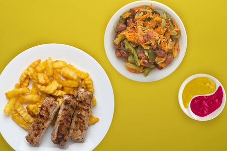 pork ribs and potatoes on a white plate with salad and sauce on a yellow background. Top view of fast food. unhealthy food.flat lay