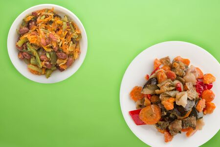 vegetable stew on a white plate. stewed vegetables on a lime background. vegetarian food.flat lay 写真素材
