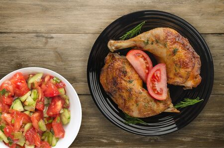 Chicken thigh with vegetables on a wooden background. chicken leg on a plate
