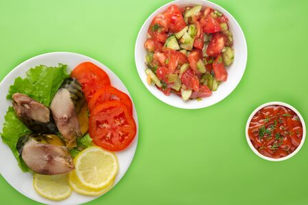 sliced mackerel with lettuce, tomatoes and lemon on a white plate with vegetable salad on a light  green background. sliced mackerel with vegetables on a plate top view. seafood flat lay