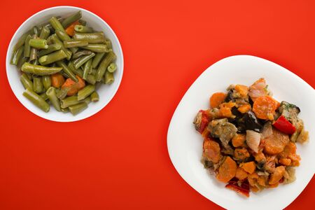 vegetable stew on a white plate. stewed vegetables on a red background. vegetarian food.flat lay