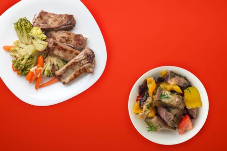 fried pork ribs with broccoli, carrots and garlic on a white plate. fried pork ribs with vegetable salad on a red background. hearty rustic food top view.flat lay