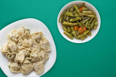 dumplings on a white plate on a green background. Top view of dumplings with vegetable salad. Asian cuisine flat lay