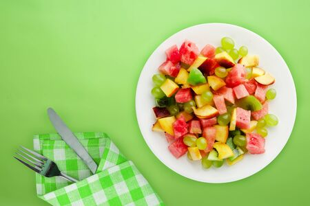 healthy food. fresh fruit salad on a white  plate. vegan food on the lime  background.