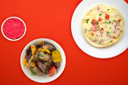 omelet on a white plate with vegetable salad and sauce on an red background. healthy breakfast top view. rustic food