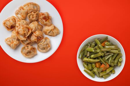 dumplings on a white plate against a red background. Dumplings meat in tomato sauce with vegetable salad top view. Asian cuisine 写真素材