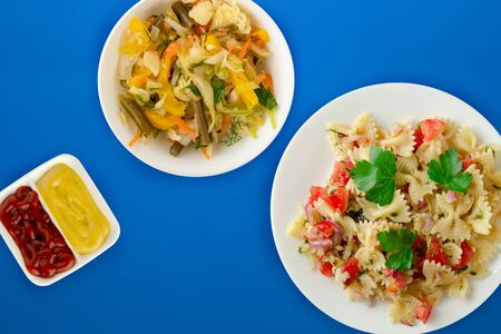 pasta on a white plate with vegetables. Mediterranean food with vegetable salad and sauce on the blue  background. healthy food falt lay