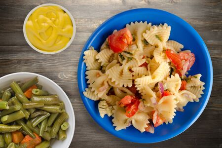 pasta on a plate. pasta tomatoes, onions, cabbage on a wooden background.healthy food