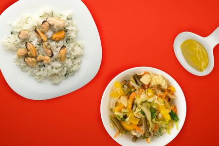 white rice with dill and mussels on a white plate. rice in vegetable salad on a red background top view. Asian cuisine.flat lay