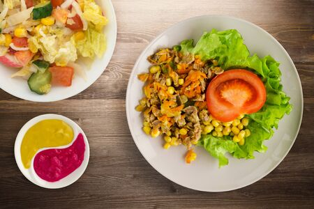salad with chicken stomachs with carrots and corn and salad on a plate. chicken salad with vegetables on a wooden background