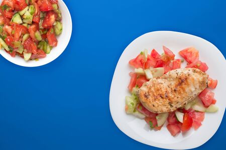 Grilled chicken breast with tomato salad, cucumbers and onions. Grilled chicken breast on a white plate on a blue green background. fried chicken breast top view.flat lay