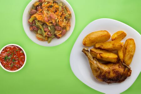 grilled chicken and french fries on a white plate on a lime background with vegetable salad and sauce. Fast food top view. unhealthy food