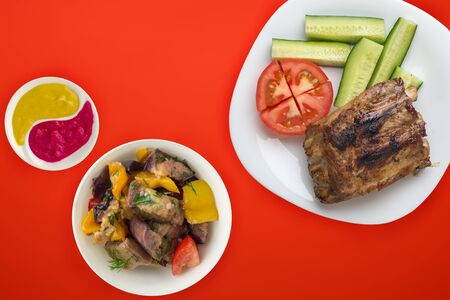 fried pork ribs with chopped cucumbers and tomatoes on a white plate. pork ribs in salad and sauce on a red background. fried ribs on top.flat lay