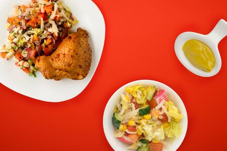 fried chicken thighs with vegetables on a white plate on the red  background. fast food with vegetable salad top view. unhealthy food .flat ley Banco de Imagens