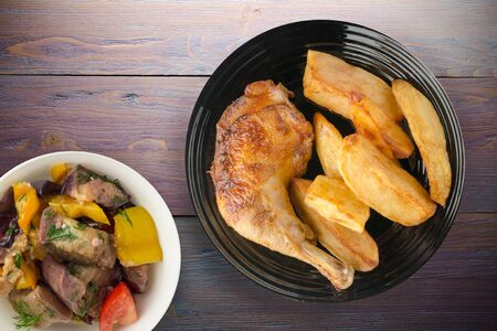 Chicken thigh with French fries on a wooden background. chicken thigh on a plate. rustic food Banco de Imagens