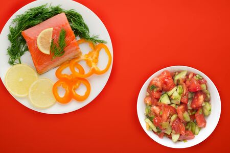 red fish with dill, pepper, lemon on a white plate on the red background. red fish with vegetable salad .sea food. flat lay