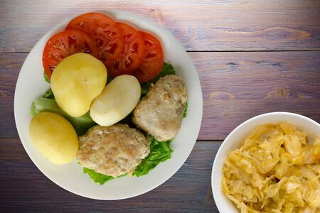 cutlet with potatoes on a white  plate. cutlet with potatoes on a wooden background