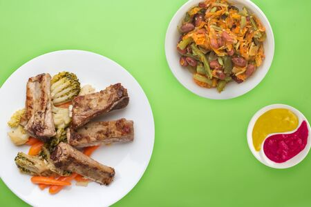 fried pork ribs with broccoli, carrots and garlic on a white plate. fried pork ribs with vegetable salad on a lime background. hearty rustic food top view.flat lay