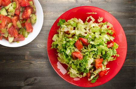 vegetarian food . salad of cabbage tomato on a red  plate on a wooden background. healthy food Stock Photo