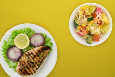 grilled chicken with vegetables lemon, salad, onion) on a yellow background. grilled chicken fillet on a plate in a vegetable salad top view.flat lay
